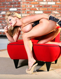 Kelly masturbates and plays with her big tits on a red couch with a red dildo.